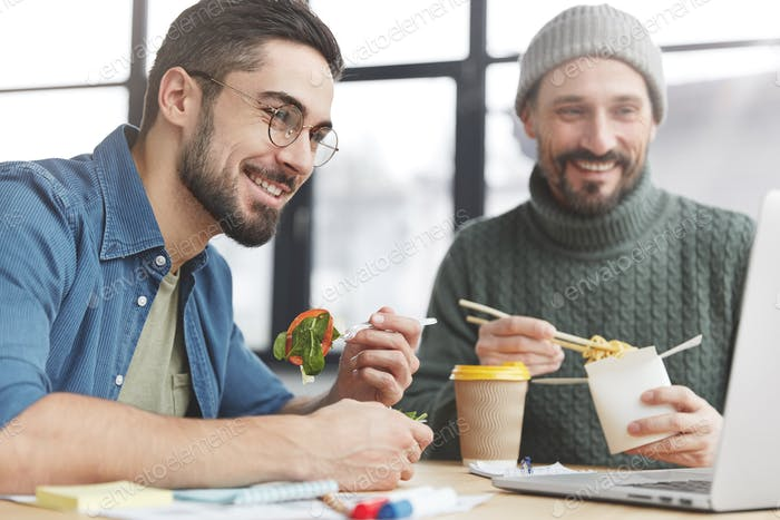 Two men freelancers have different nutrition: one keeps to diet and eats only healthy food, other pr