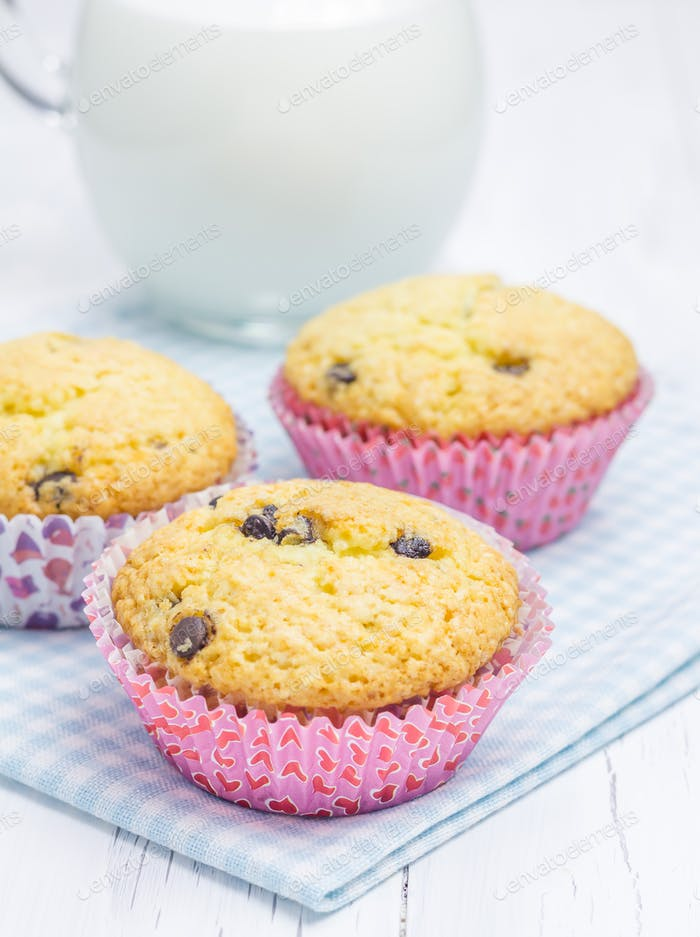 Homemade muffins with choco chips and jar of milk