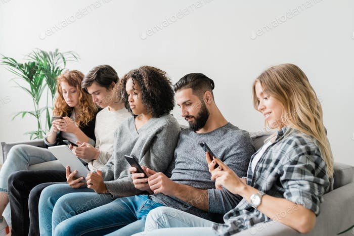 Five casual intercultural friendly millennials scrolling in their mobile gadgets