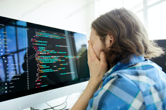 Stressed computer programmer in front of computer