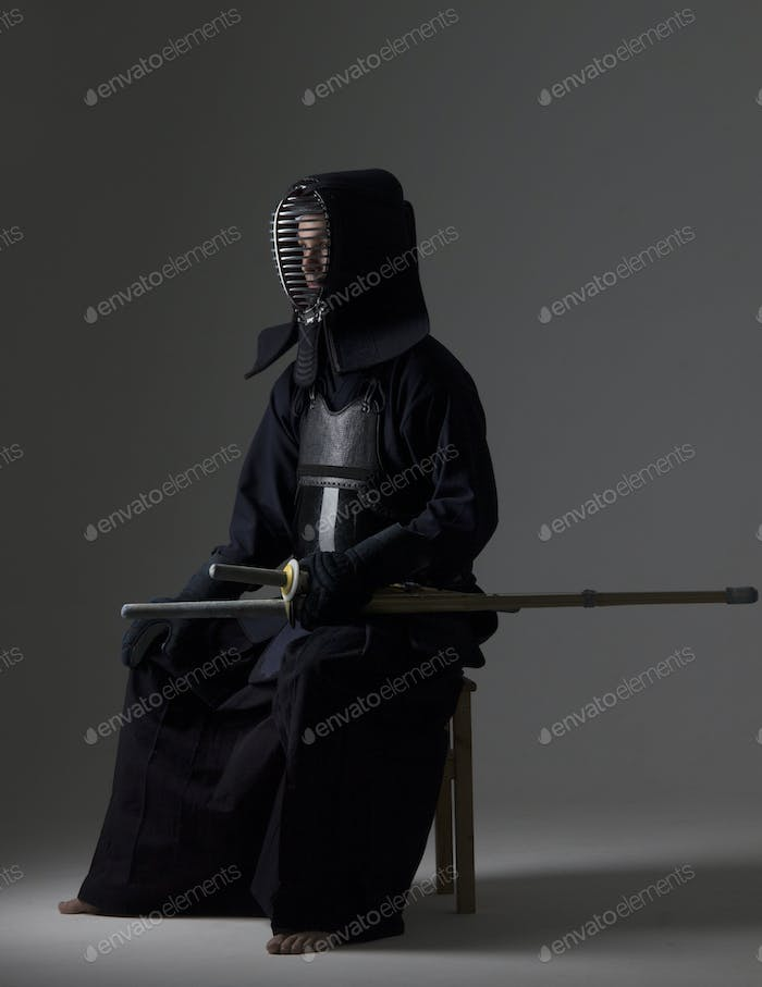 Portrait of man kendo fighter with bamboo sword in traditional uniform.