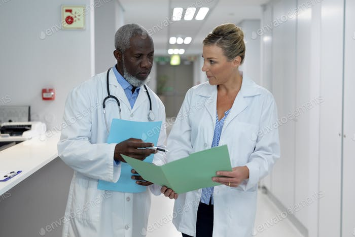 Diverse male and female doctors standing in hospital corridor looking at medical documentation