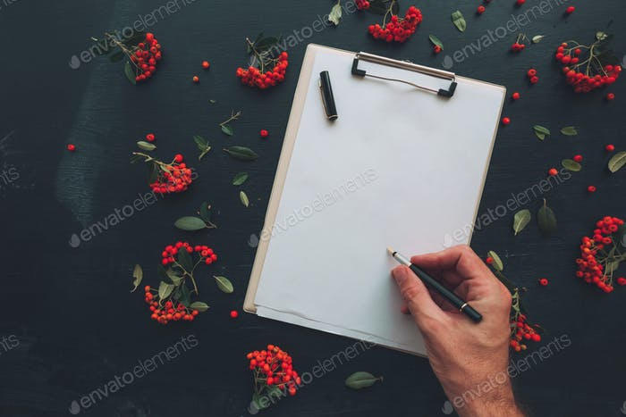 Flat lay of hand writing on clipboard notepad paper