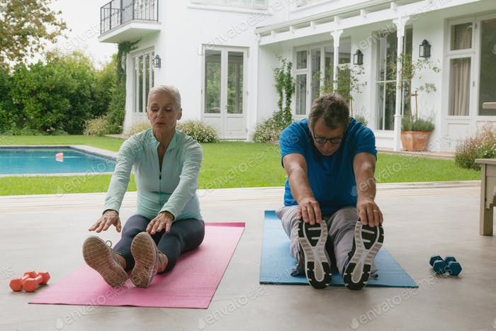 Determined active senior Caucasian couple doing stretching exercise in the porch at home