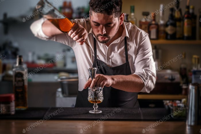 Barman pouring mixture into a jigger