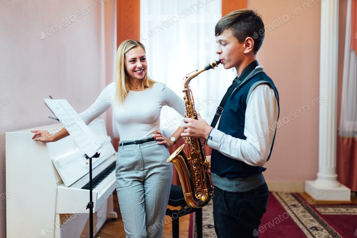 Cheerful teacher with student boy learning saxophone lessons at school