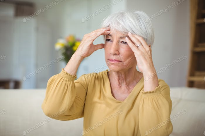 Senior woman suffering from head ache in living room