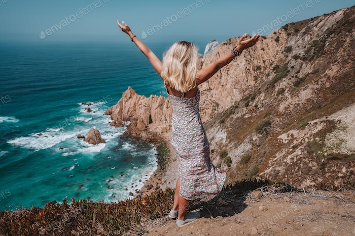 Beautiful women raising hands enjoying impressive Praia da Ursa Beach. Surreal scenery of Sintra