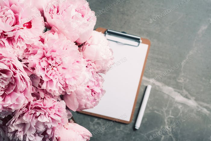 Fashion feminine blogger concept. Feminine workspace with notebook, clipboard, paper, pink peony
