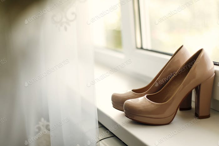 beautiful beige shoes on the window in the morning, bridal morning, wedding preparation