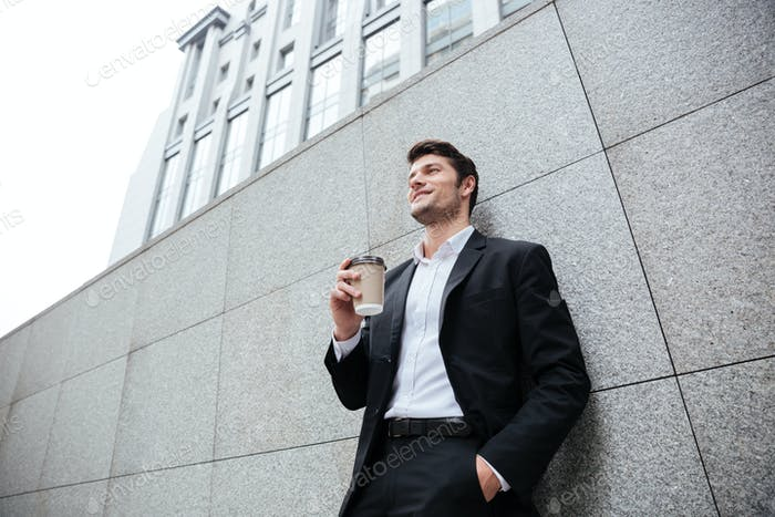 Cheerful young businesman drinking coffee outdoors