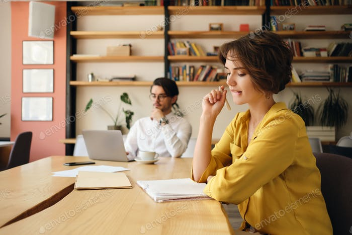 Young attractive woman at the table with notepad dreamily working with colleague in office
