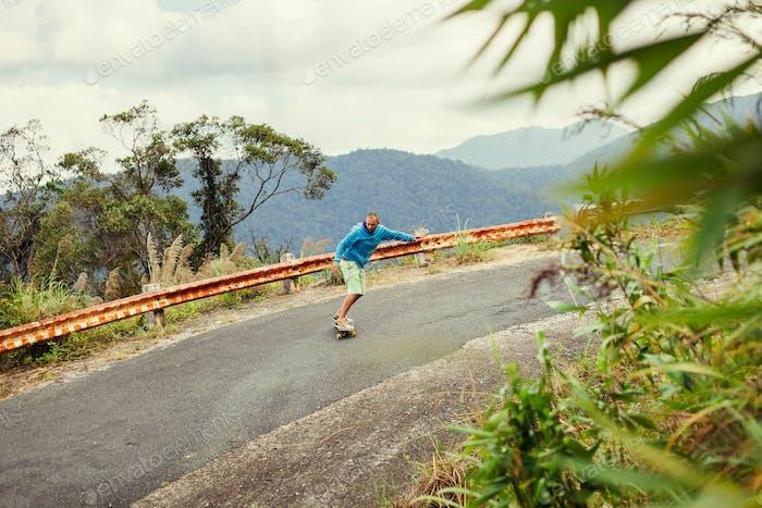 Hipster Mann Longboarding extrem in Tropen