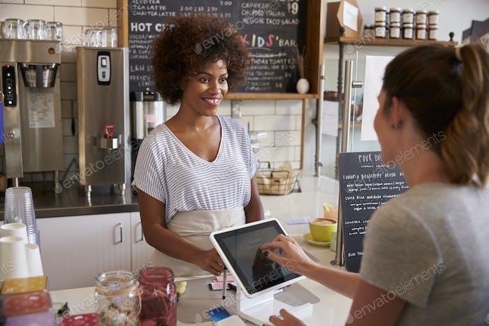Cliente en el mostrador de la cafetería paga Uso Completa táctil