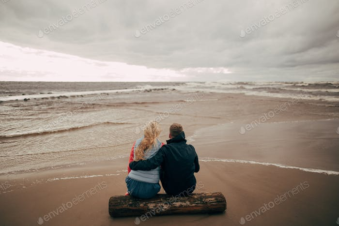 back view of young couple sitting on log and looking at beautiful wavy Baltic sea