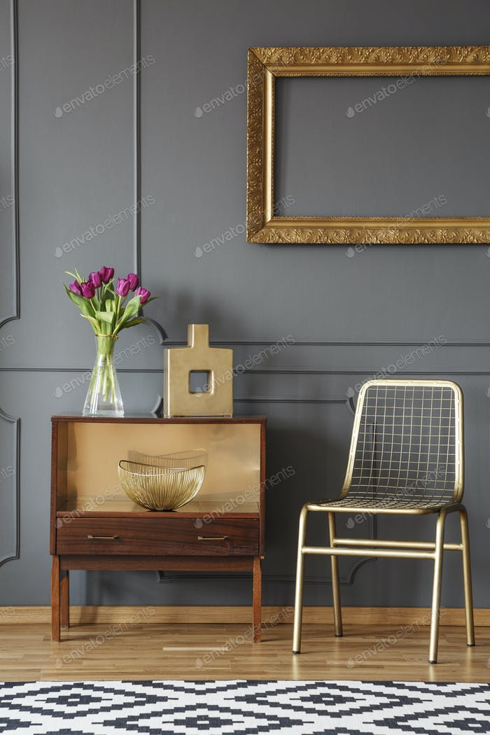 Gold chair next to wooden cabinet with flowers in grey interior