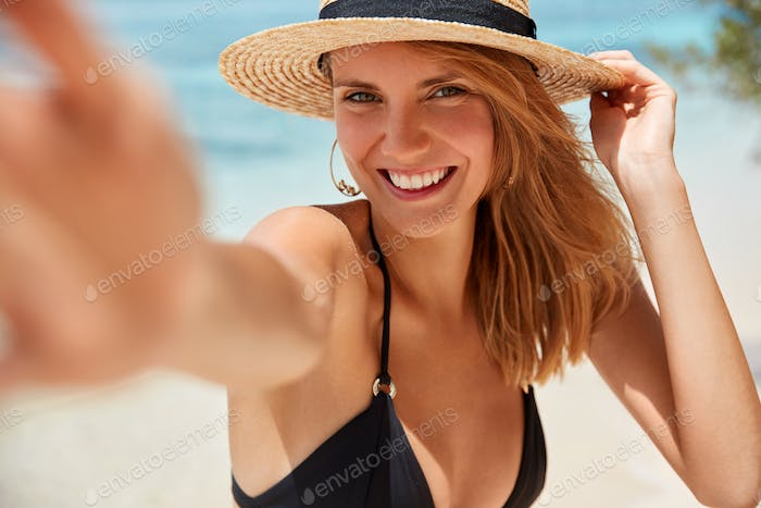 People, lifestyle, happiness and summer time concept. Lovely young smiling woman with cheerful expre