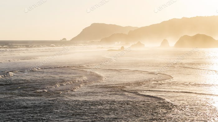 Sunset landscape with huge waves and mountain hills on horizon