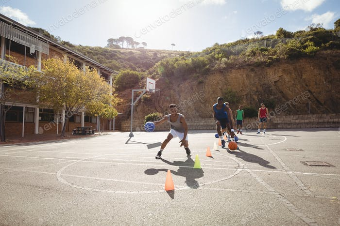 Basketball players practicing dribbling drill