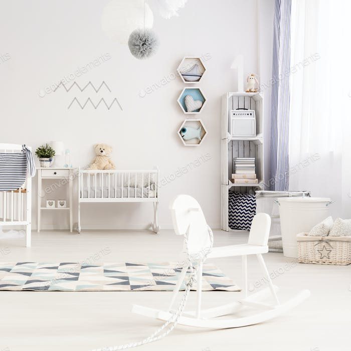 Unisex nursery with wooden rocking horse