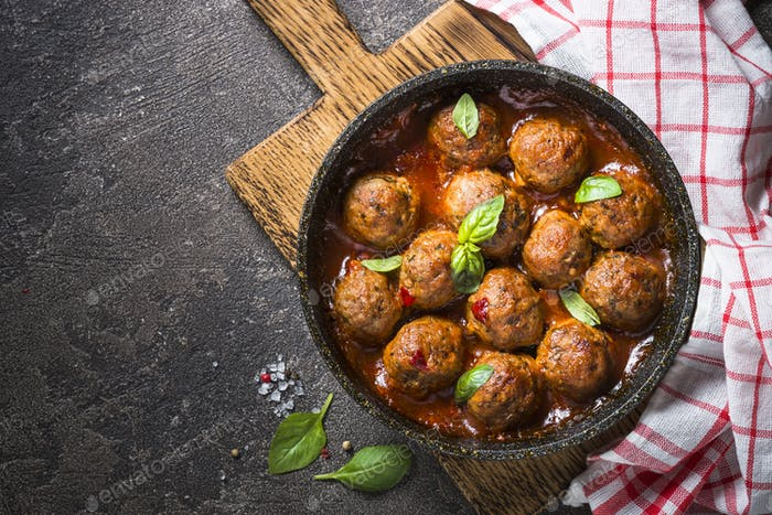 Meatballs in tomato sauce in a frying pan on dark stone table