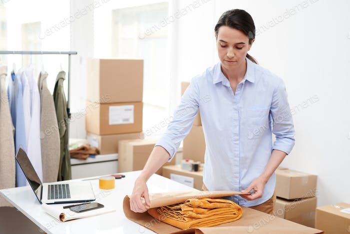 Young manager of online shop wrapping folded yellow trousers into paper
