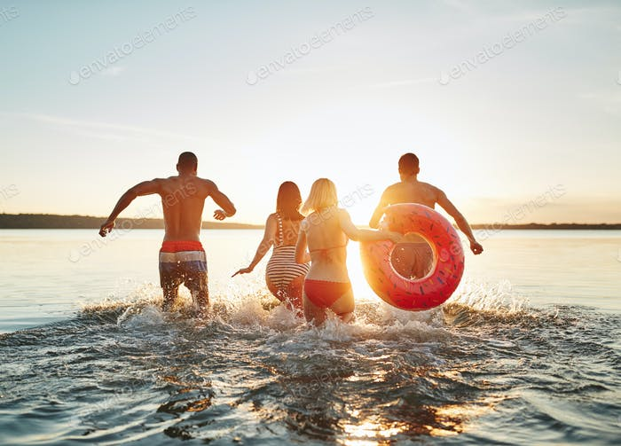 Young friends running and splashing into a lake at sunset
