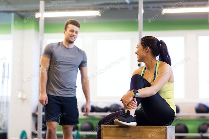 happy man and woman with heart rate tracker in gym