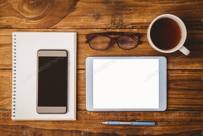 Smartphone on notepad next to tblet and glasses and cup of coffee on wooden table