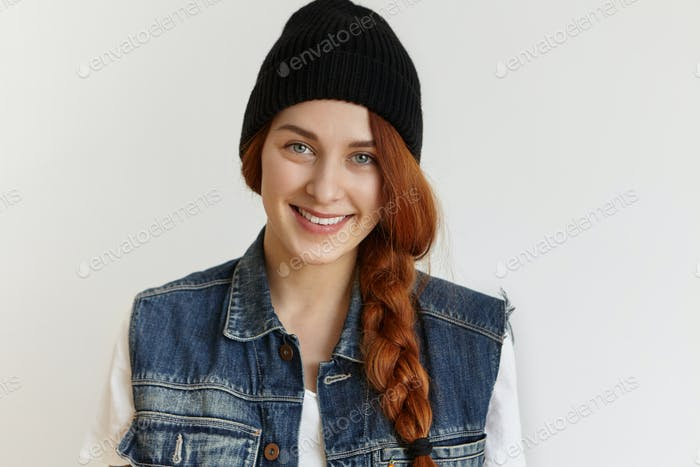 People and lifestyle concept. Portrait of beautiful cheerful redhead girl wearing stylish black wint