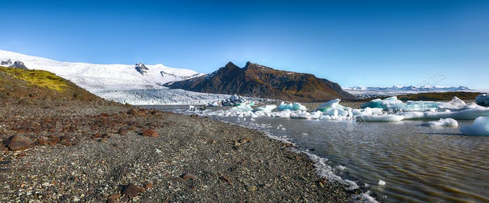 Panoramic view of melting icebergs floating in the Fjallsarlon glacial lake