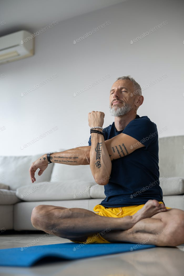 Male with tattoos is stretching his hand