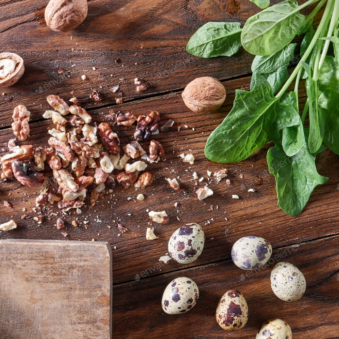Fresh spinach, quail eggs, pieces of nuts on a wooden table with copy space. Healthy Salad