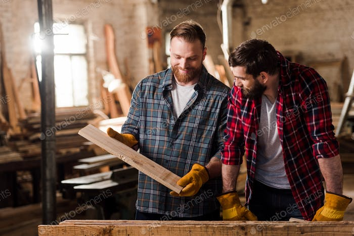 happy carpenter in protective gloves showing wooden plank to partner at sawmill
