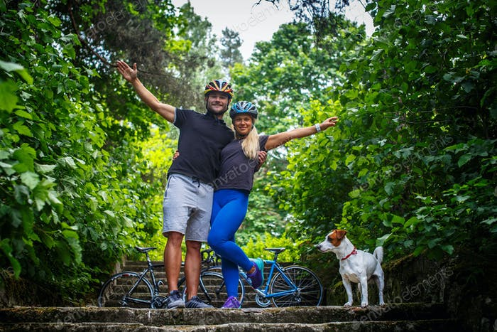 Man and woman in cyclist helmets posing on steps