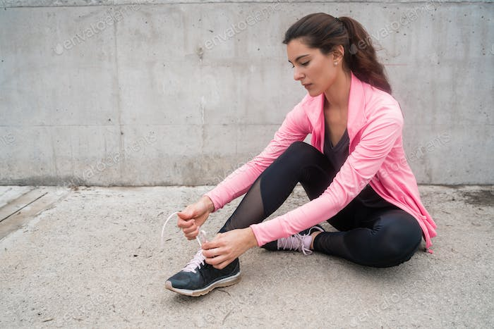 Athletic woman  tying her shoelaces.