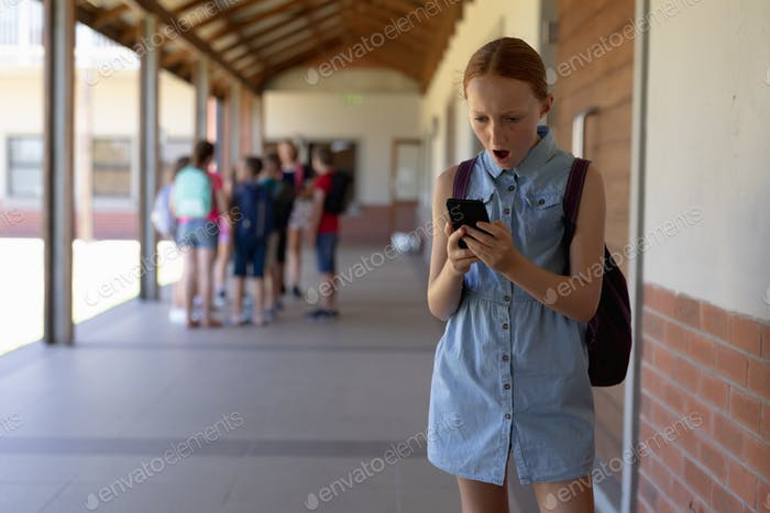 schoolgirl standing in the schoolyard at elementary school using a smartphone
