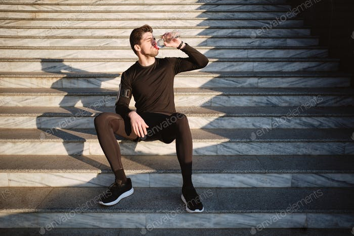 Young attractive sporty man sitting on stairs drinking water after workout outdoor