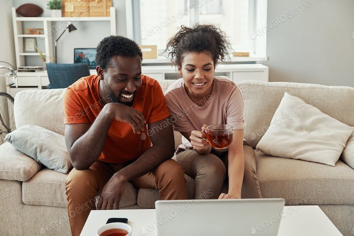 Beautiful young African couple looking at laptop and smiling while spending time at home