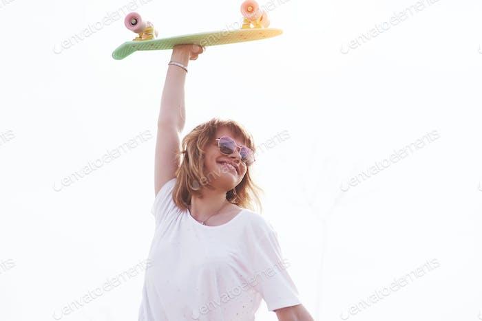 Schöne Teenager-weibliche Skater sitzt auf Rampe im Skatepark. Konzept der städtischen Sommeraktivitäten