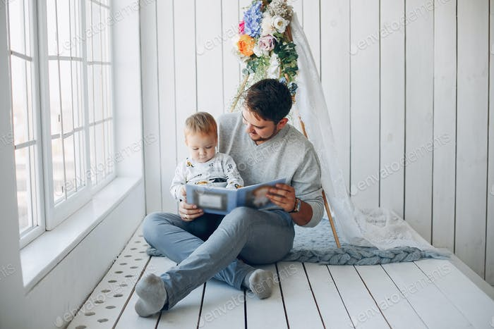 Father sitting at home with little son