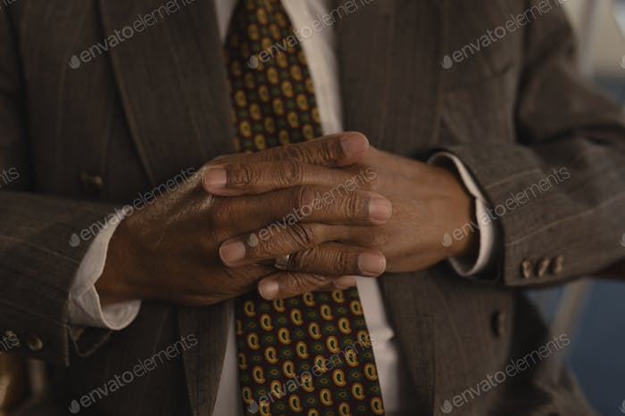 Mid section of senior man with hands clasped at nursing home