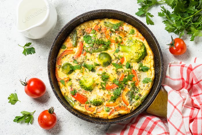 Frittata with vegetables on white stone table