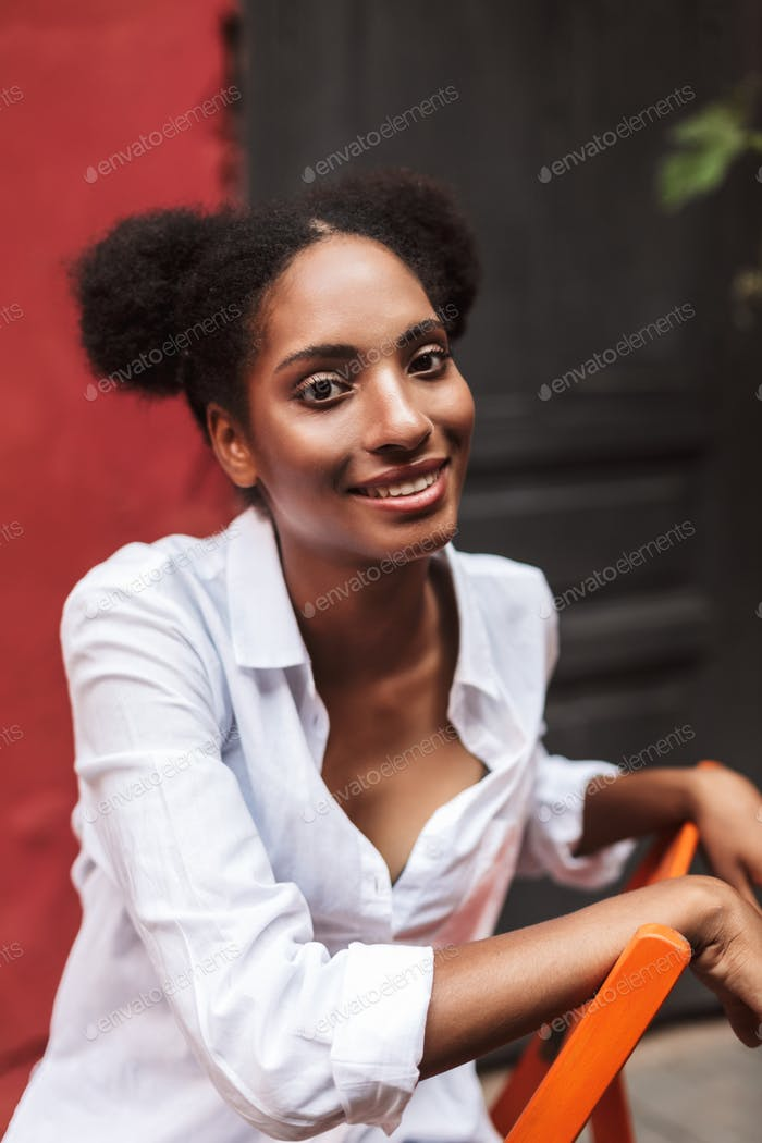 Beautiful smiling african girl with dark curly hair in white shi