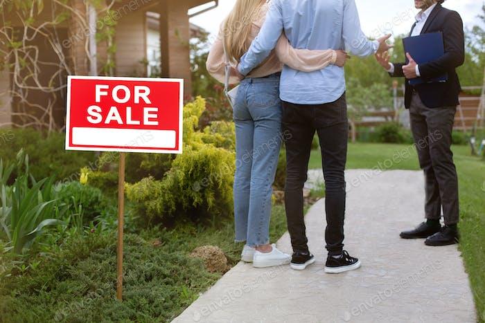 Unerkennbares junges Paar mit Immobilienmakler Blick auf Wohnimmobilien zum Verkauf, außerhalb