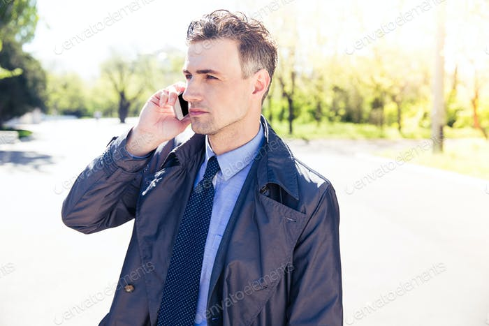 Confident businessman talking on the phone outdoors