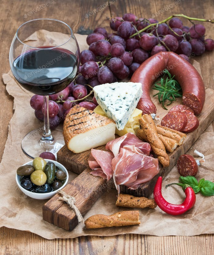 Glass of red wine, cheese and meat board, grapes, fig, strawberries, honey, bread sticks