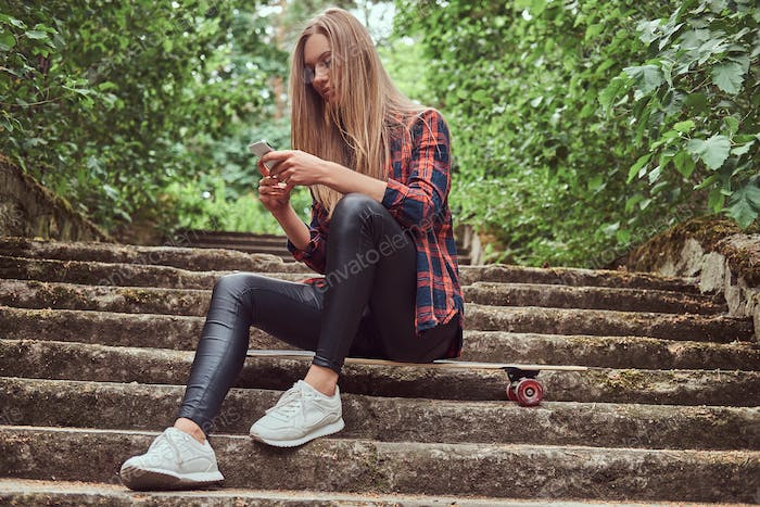 Young blonde hipster girl using a smartphone while sitting on steps in a park.