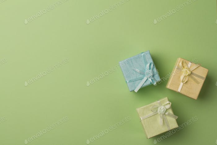 small gift boxes on green paper background