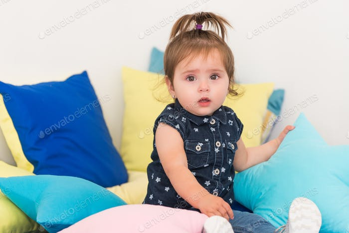 Charming cute two year old girl sitting on pillow